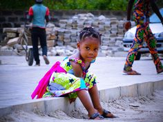 child - girl - smile - vehicle - transportation - car - ground - road - paving stone - people - sand - city - worker