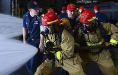 Sailors are firefighters too! Sailors aboard USS Nimitz perform an exercise during a damage control competition in the hangar bay.