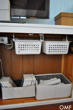 $1 plastic baskets hung from cup hooks under the shelf. Absolutely brilliant way to use a deep cabinet!