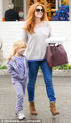 Cute: Her daughter, five, kept out the chill in a lilac coloured tracksuit, and wore a pair of white trainers