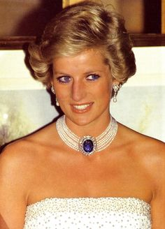 This egg of a sapphire surrounded by diamonds was a brooch given to Diana by the Queen Mother as a wedding present. Though she wore it a couple times as a proper brooch, she soon performed some jewelry magic and stuck it in the center of seven strands of pearls.