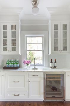 Gorgeous white butler's pantry features a Thomas O'Brien Clark Ceiling Light illuminating glass-front upper cabinets and white lower cabinets fitted with glass-front wine fridge paired with a white gloss subway tiled backsplash and calcutta marble countertops framing a small round prep sink under window.