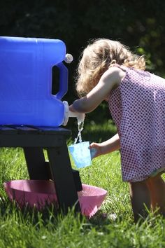 toddler pouring water from camping water carrier