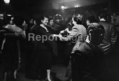 Women dancing together at The Gateways Club or 'The Gates' in Chelsea in 1953, one of the few places where lesbian women could meet openly and be together in the post-war years in Britain. Playing on the piano is Jack London, the first black athlete to win Olympic medals for Great Britain. - Alan Vines - 1953-03-14