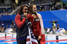 Gold medalist Simone Manuel of the United States (L) and gold medalist Penny Oleksiak of Canada celebrate during the medal ceremony for the Women's 100m Freestyle Final on Day 6 of the Rio 2016 Olympic Games at the Olympic Aquatics Stadium on August 11, 2016 in Rio de Janeiro, Brazil.