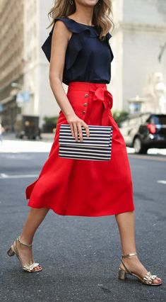 Navy sleeveless top with ruffled collar (open back) paired with bright red high waisted a-line midi skirt. The skirt features three decorative side buttons on a stitched down panel (presumably both sides) and big front waist tie. Nod to sailor style. Clutch is horizontally striped in white and navy. Gold ruffled block heel sandals. Style Planet