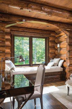 Attention to detail was paid in every one of the log home's abundant spaces, including this daybed/reading nook tucked into a bump-out in one of its seven spacious bedrooms. #windowseat #loghome #rustic #luxe