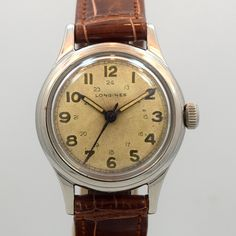 A 1947 vintage Longines post WWII-era, stainless steel timepiece. This 32mm wide watch features a patinated silver dial with luminous Arabic numerals, a 24-hour inner track, and a manual caliber 23M movement to boot. (Store Inventory # 10003, listed at $1