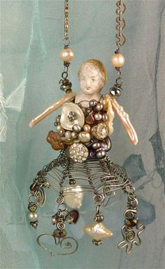 A wire-woven doll necklace built on a small porcelain doll body, using wire, vintage rhinestone buttons, beads, and pearls.