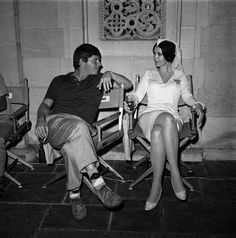 Full BTS shot of Robert Morse as Dennis Barlow and Anjanette Comer as Aimee Thanatogenous; both seated in director's chairs./ The Loved One / 1965