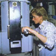 Princess Diana looking through a scope in a submarine.