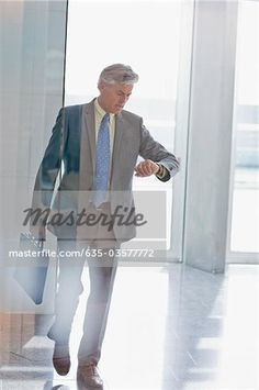 Businessman walking and checking the time on wristwatch