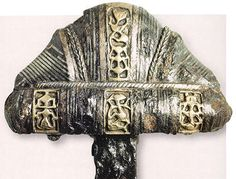 Viking age / A Viking sword hilt with a cocked hat or lobed pommel. The decoration includes stamped abstract cartouches.