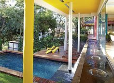 O arquiteto Leo Romano manteve as árvores no terreno em declive e projetou o paisagismo com plantas tropicais e espelho-d'água com queda para a piscina. Assim, as áreas internas e externas parecem se confundir.