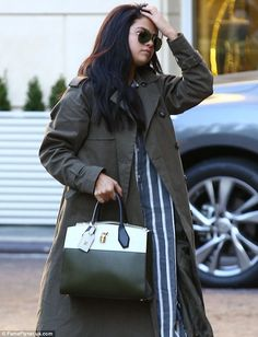 Covered up: Selena Gomez wore a large green trench coat on Thursday while arriving at a hotel in Beverly Hills, California