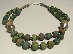 Tribal Gallery Designs   Necklace; Ancient green Hebron or Kano beads from the Dead sea, they are more than 300 years old.  these are combined with Tuareg metal bicone beads, coin silver spacers and green vulcanite heishi discs.