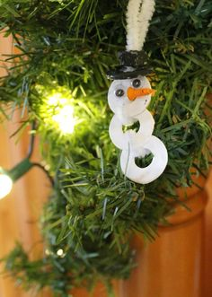 This unique snowman craft for kids is fun and simple!  Use washers, nuts, and a screw to make a cute Christmas ornament, necklace, or homemade gift!  www.HowWeeLearn.com