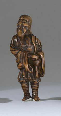 "WOOD NETSUKE Early 19th Century In the form of a bearded sennin standing and peering heavenward. Metal-inlaid eyes. Height 3.5"" (9 cm)."