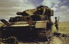 "demons: "" El Guettar, Tunisia "" Fallschirmjager: A Panzerkampfwagen IV Ausf.G of the Deutsche Afrika Korps (Panzergruppe Afrika) having taken a hit and ""brewed"" up, being inspected by men of the U.S. Army II Corps, 1943."