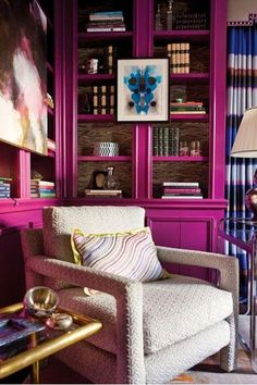 Painting a bookcase in a bold hue — and then using its frame to display art — turned this would-be boring corner into a fantastic (fuchsia!) focal point.