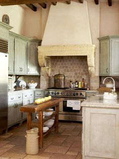 French kitchen in pastel colours. Mint-washed cabinets, narrow wooden island, and exposed brick accents. #home #kitchen #french #kitchenspace