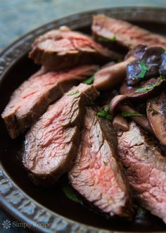 Grilled flank steak with a sauce of assorted mushrooms, sautéed with butter and shallots and cooked down in a red wine reduction. Great for #MemorialDay!~ SimplyRecipes.com