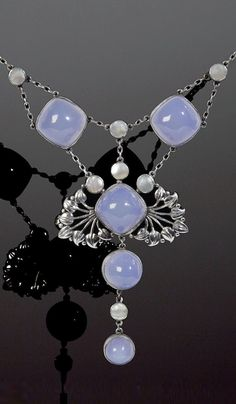 An Arts and Crafts chalcedony set pendant necklace. The central cushion-shaped blue chalcedony cabochon framed by pierced panels of stylised foliage, suspending a blue chalcedony drop, highlighted by mother o' pearl, with similarly set chain-link swags above, to trace-link back chain with ropetwist decorated T-bar fitting, unsigned, length 39cm. #ArtsAndCrafts #necklace