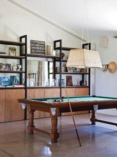 Sector de juegos en un living. Mesa de pool de madera, lámpara con pantalla rectangular de mimbre y modular con estantes y espejo.