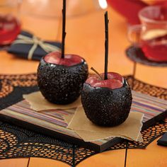 Basic Black Sparkles Dipped Apples from @michaelsstores.  Deep red apples covered in Wilton® Black Caramel Dip and Wilton Black Sparkles create spine-chilling Halloween treats.