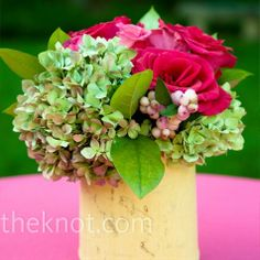 Small, wooden vases filled with green hydrangeas, white berries and fuchsia roses spruced up high-top tables on the lawn outside the reception tent.