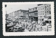 Facing West, this photograph shows a parade marching Eat down Broadway.