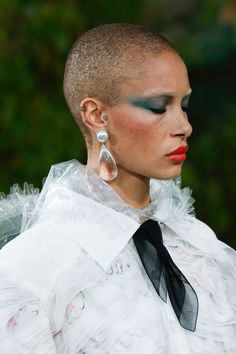 Tom Pecheux created a bold beauty look at Chanel, comprising blue eyeshadow applied right up to the brows, peachy blush, and glossy pink-red lips.