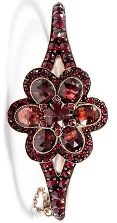 Garnet bracelet, in the shape of a flower, around 1890. Faceted garnets, max. 5.6 x 8.3 mm, bangle max. 2.8 cm wide, inside diameter 4,8 x 5,8 cm