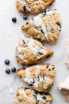 Deliciously flaky, crumbly, tender blueberry scones with vanilla icing. The secret is frozen butter and COLD heavy cream! Recipe on sallysbakingaddiction.com