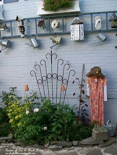 Repurposed old ladder creates a hanging display of birdhouses and watering cans