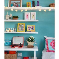 Esse quarto de menina adolescente é ao mesmo tempo feminino e contemporâneo. O cordão de luminárias deu um toque romântico. Papel de parede e almofadas Espaço Multi.