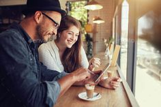Happy couple in a coffee shop using digital tablet by jacoblund. Happy couple in a coffee shop surfing internet on digital tablet. Young man and woman in a restaurant looking at touc...