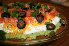 Classic 70s 7-Layer Dip - A retro throw-back to the 70s, 7 layer dip is made with refried beans, avocado or guacamole spread, sour cream, shredded cheese, tomatoes, black olives and green onion, and is still a party favorite.
