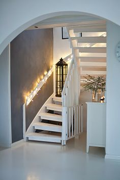 Grey and white stairs area. Nicely placed lights and lantern.