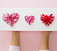 Valentine String Art With Kids. Recycle a box to make a pretty string art display of hearts! Great fine motors Valentine activity for kids.