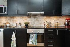 Muebles de cocina negros y pared de piedra