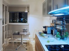 Transparent furniture and reflective backsplash cleverly creates a more open space