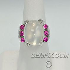 $1450 Large and luminous moonstone cabochon flanked by 6 dazzling pink tourmalines. Heavy, solid setting is highly polished 14KT white gold with 4 double prongs. Moonstone measures 13.6 X 16.4mm. 6 Pink tourmalines measure 3.3mm each. Ring is handmade, one of a kind and is a size 7 1/2. Gemfix.com