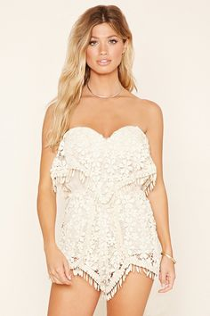 A strapless romper from Selfie Leslie™ crafted from floral knit crochet with padded cups, an exposed back zipper, an elasticized waist, a flounce-layered front, and scalloped trim.
