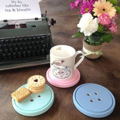 A gorgeous hand-painted wooden button coaster.Please note: ribbon may not be as shown in the photo.This marvelously useful giant button coaster is fantastic for stopping dirty marks on surfaces and will add a quirky touch to your home. The perfect little gift for someone as cute as a button. Available in cornflower, turquoise or pink. Please note as this product is hand-painted there may be small imperfections, which make each button unique.Handmade in England. Hand-painted wood. Wipe clean…