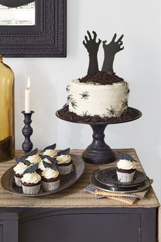 """The eye-catching """"Help Me!"""" cakeis simply a store-bought white cake with a few dark twists. (Talk about hands-off!)Start with a store-bought frosted layer cake. Cut out a pair of arms and hands in black craft paper and tape to skewers to help them stand upright. Pile on a mound of """"dirt""""— crumbled chocolate cookies—to give it that """"buried alive"""" vibe.Top vanilla-frosted cupcakes with edible fondant raven feathers (piratedessert.etsy.com).For an extra hair-raising element, add plastic…"""