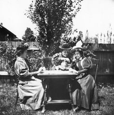 A woman pours tea for her friends seated outdoors at a table (c. 1890).