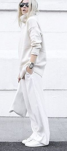 A white funnel neck sweater and white trousers