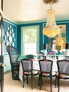 Atlanta Homes & Lifestyles::..::April 2013-Behind black lacquer doors, the dining room's bold color palette is the perfect foil for the Murano glass chandelier. The dining room chairs are upholstered in Schumacher's Chiang Mai Dragon fabric. The table runner belonged to Cinda's grandmother.