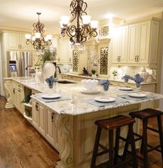 FRENCH COUNTRY GRAND KITCHEN WITH GRAND ISLAND, DECORATIVE CABINETS WITH WROUGHT IRON INSERTS, AND ACCENT LIGHTING